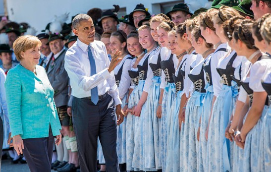 German Chancellor Angela Merkel, left, and U.S. President Barack Obama, second left, are welcomed by local residents in their traditional costumes during their visit in the village of Kruen, southern Germany, Sunday, June 7, 2015, prior to the G-7 summit in Schloss Elmau hotel near Garmisch-Partenkirchen. (Marc Mueller/Pool Photo via AP)