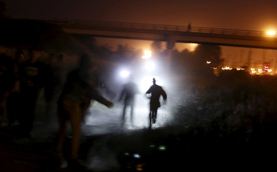Migrants are illuminated by police torches as they run to cross a fence during an attempt to access the Channel Tunnel in Frethun, near Calais, France, August 5, 2015. REUTERS/Juan Medina      TPX IMAGES OF THE DAY