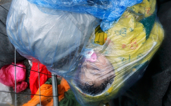 A migrant's child sleeps as it is seen in a rain cover at the border crossing from Slovenia in Trnovec, Croatia October 19, 2015. The Balkans faced a growing backlog of migrants on Monday, thousands building up on cold, wet borders after the closure of Hungary's southern frontier diverted them to Slovenia. REUTERS/Antonio Bronic TPX IMAGES OF THE DAY