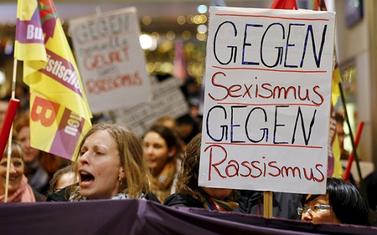 Women hold up placards during a protest in the Cologne main railways staion